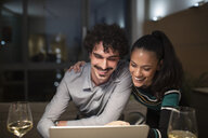 Happy couple using laptop and drinking white wine at home at night - CAIF22675