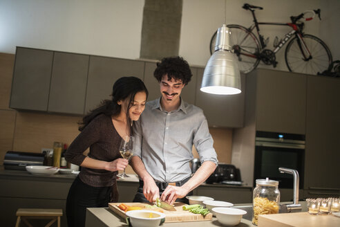 Couple cutting vegetables, cooking dinner in apartment kitchen - CAIF22690