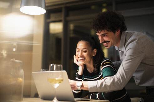 Happy couple using laptop and drinking white wine at home at night - CAIF22696