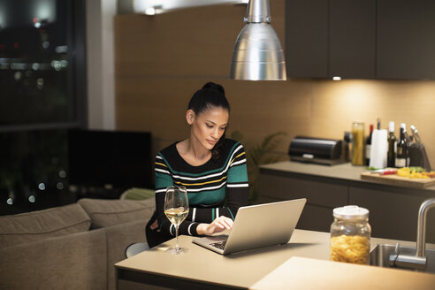 Focused woman using laptop and drinking white wine in apartment kitchen at night - CAIF22699