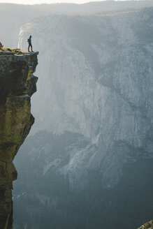 Mid distant view of hiker standing on cliff at Yosemite National Park - CAVF61064