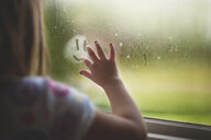 Cropped image of girl making anthropomorphic smiley face on wet window at home during rainy season - CAVF61067