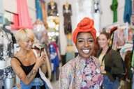 Portrait enthusiastic young woman shopping with friends in clothing store - CAIF22703