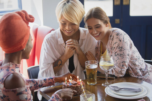 Young women friends celebrating birthday with cake in restaurant - CAIF22706