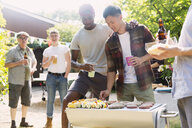 Male friends enjoying barbecue in sunny summer backyard - CAIF22745