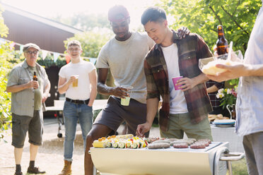 Male friends enjoying barbecue in sunny summer backyard - CAIF22745