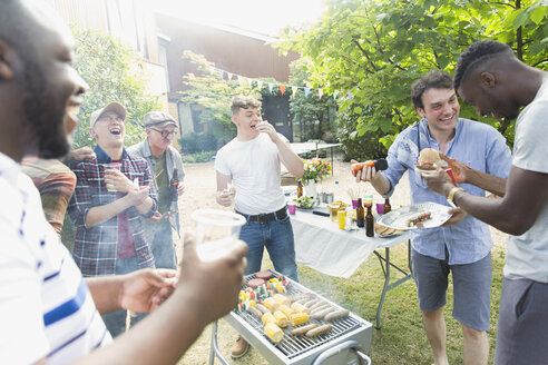 Male friends laughing and eating around barbecue grill in backyard - CAIF22748