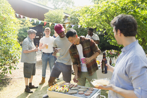 Male friends drinking beer and barbecuing in sunny summer backyard - CAIF22751
