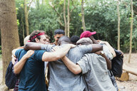Men friends hugging in huddle on hike in woods - CAIF22760