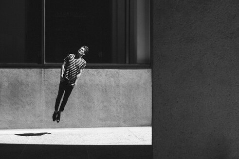 Young man jumping on urban sidewalk - CAIF22772