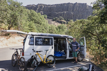 Portrait confident man with mountain bikes at van in remote parking lot, Hood River, Oregon, USA - CAIF22775