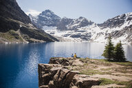 Couple sitting on cliff overlooking tranquil, sunny mountains and lake, Yoho Park, British Columbia, Canada - CAIF22784