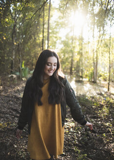 Happy teenage girl looking down while walking against trees in forest - CAVF61075