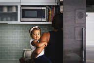 Rear view of mother carrying cute daughter while standing in kitchen at home - CAVF61141