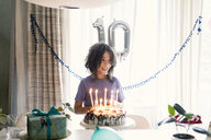 Happy boy looking away while standing by birthday cake against window at home - CAVF61144