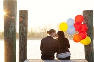 Rear view of couple with balloons kissing while sitting on pier - CAVF61153
