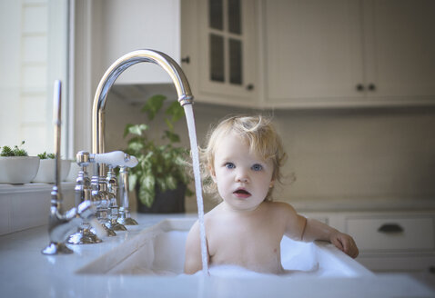 Portrait of cute shirtless girl bathing in sink at home - CAVF61222
