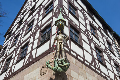 Germany, Nuremberg, Golden statue on a half timbered house in the medieval town center - RUNF01377