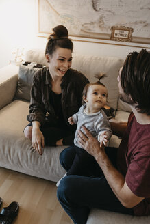 Happy family with baby girl in living room at home - LHPF00447