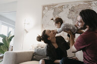 Happy family playing with baby girl in living room at home - LHPF00450