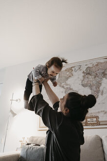 Happy mother playing with baby girl in living room at home - LHPF00453