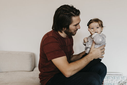 Father holding baby girl at home - LHPF00459
