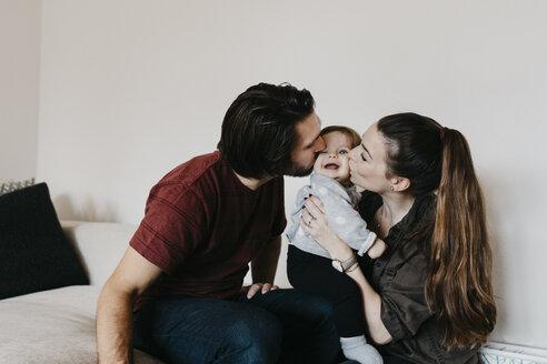 Parents kissing baby girl at home - LHPF00462
