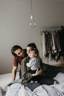 Happy family with baby girl sitting on bed at home - LHPF00465