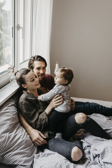 Happy family with baby girl sitting on bed at home - LHPF00468
