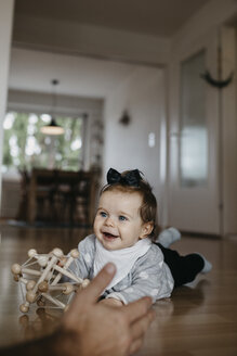 Happy baby girl lying on the floor playing with motor skill toy - LHPF00477