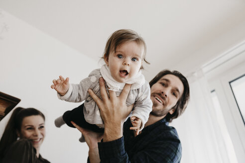 Happy family playing with baby girl at home - LHPF00486
