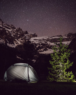 Illuminated tent on field by mountain against star field at night - CAVF61244