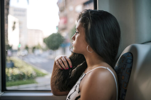 Side view of thoughtful serious woman looking through window while sitting in bus - CAVF61307