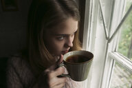 Close-up of thoughtful woman looking through window while having tea at home - CAVF61331