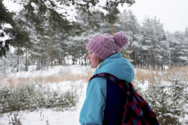 Side view of woman with backpack standing in snow covered forest - CAVF61340