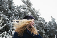 Low angle view of happy woman with blond hair looking away while standing against trees in forest during winter - CAVF61343