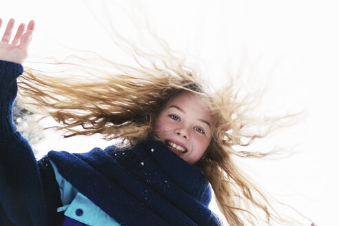 Low angle portrait of happy woman with blond hair standing against clear sky during winter - CAVF61346