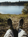 Low section of hiker sitting on field by lake in forest during sunny day - CAVF61373