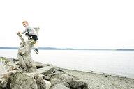 Playful boy climbing on log at beach against clear sky - CAVF61436