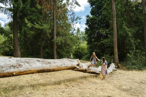 Mother assisting daughter in walking on log against trees at forest - CAVF61448