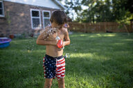 Shirtless boy playing with water bombs while standing on grassy field at backyard - CAVF61460