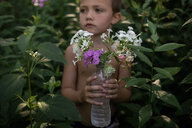 Shirtless boy holding flowers in plastic water bottle while standing amidst plants at backyard - CAVF61466