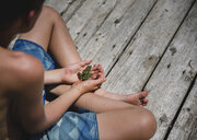 High angle view of shirtless boy holding frog while sitting on wooden pier - CAVF61475