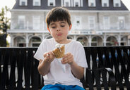 Cute boy eating ice cream cone while sitting on bench against building in city - CAVF61487