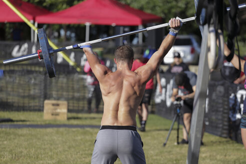 Rear view of disabled shirtless man lifting deadlift while standing at park - CAVF61490