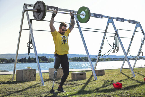 Male adaptive athlete lifting deadlift while standing against lake at park during sunny day - CAVF61502