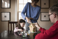 Siblings making gingerbread house on table at home - CAVF61556