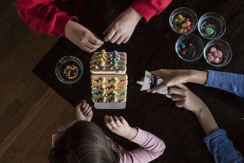 High angle view of siblings decorating gingerbread house together on table at home - CAVF61559