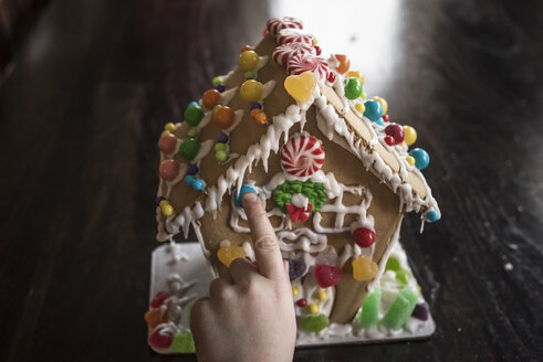 Cropped hand of girl decorating gingerbread house with candies on table at home - CAVF61562