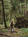 Rear view of female hiker with backpack walking in forest - CAVF61574